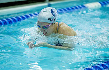 Female swimmer wearing goggles and swim cap does laps